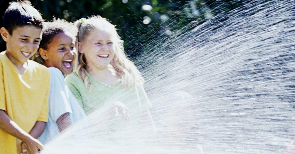 three kids playing with a hose
