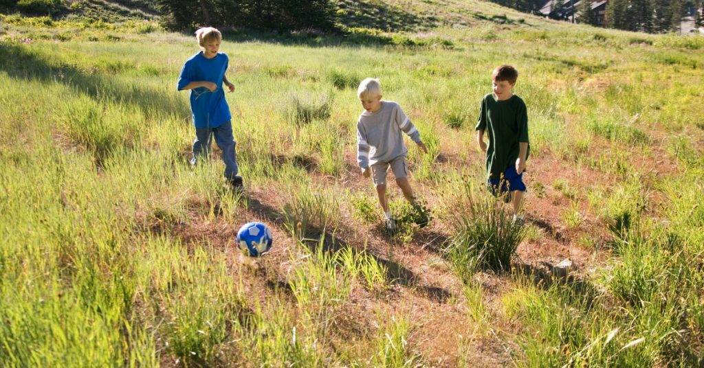 3 boys kicking a ball in a field.