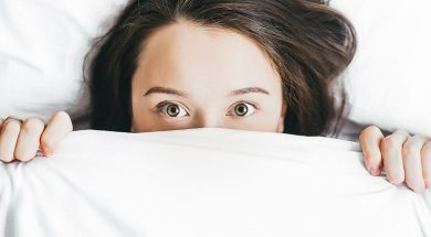 woman-peeking-out-from-under-bed-covers.jpg
