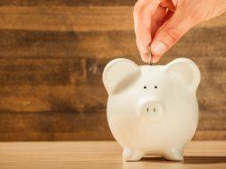 hand-putting-money-into-piggy-bank-2.jpg