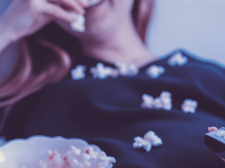 Woman-watching-TV_eating-popcorn-and-holding-remote-1200×480-1.png