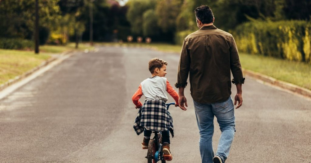 photo of a man helping his son ride a bike down the road
