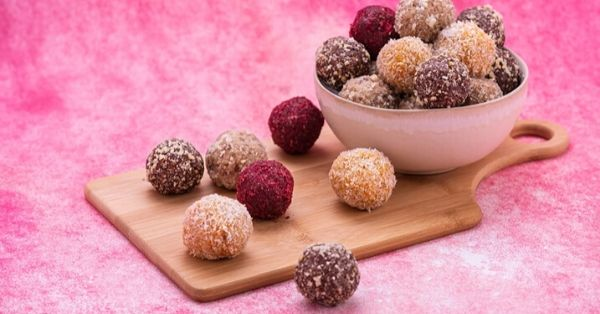 photo shows bliss balls in a bowl on a pink backdrop
