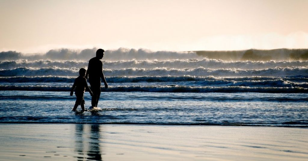 a boy walks with his dad on the beach