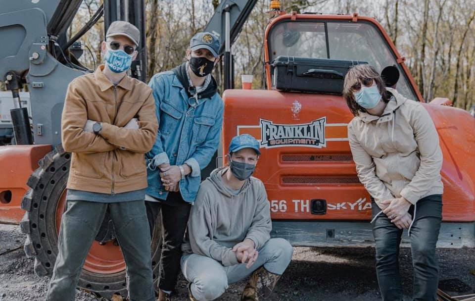 Colony House band members wearing masks posing in front of orange machinery